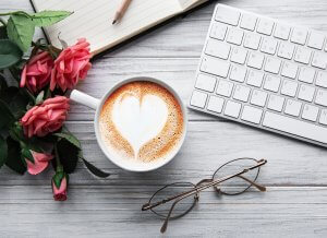 A composition of a coffee with heart shaped latte art, roses glasses and a keyboard