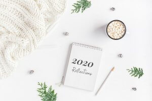 """wintery desk and notepad with a note """"2020 reflections"""""""